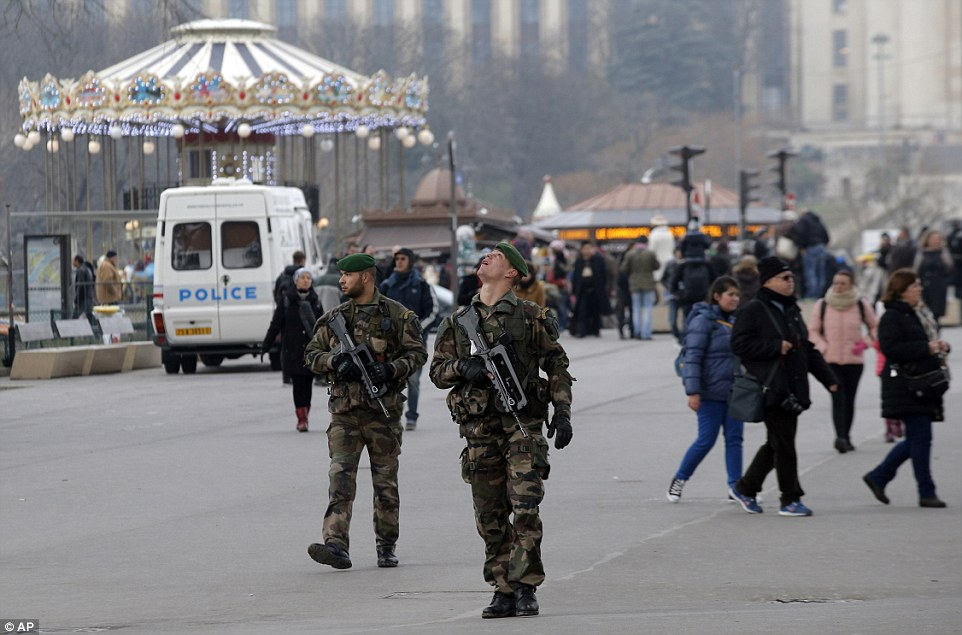 High alert: French soldiers patrol at the Eiffel Tower after the Charlie Hebdo shooting as the militants are hunted across the city