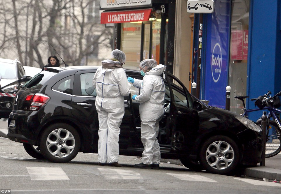 Forensic experts examine the car believed to have been used as the escape vehicle by gunmen who attacked the Charlie Hebdo office