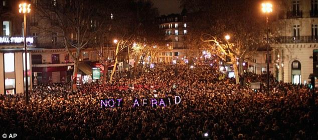 'Sin miedo': La gente se reúne para rendir homenaje a las víctimas del ataque terrorista contra el periódico satírico, en París ayer por la noche