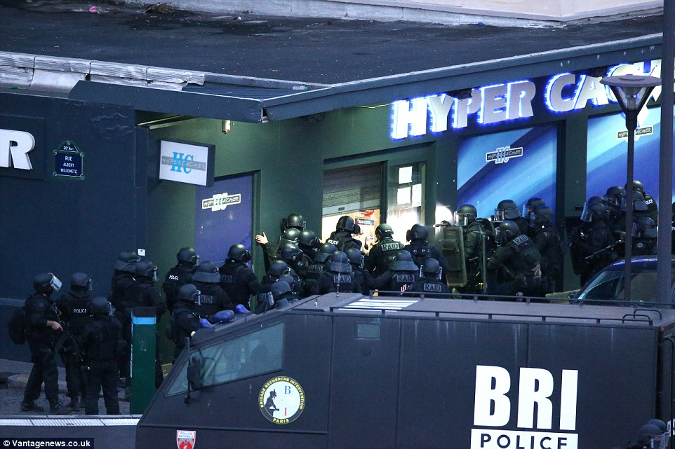Armed police swarm the entrances and exits to the Hyper Cache in eastern Paris after several shoppers were held hostage for several hours