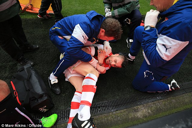Debuchy reacts after colliding  with the advertising boards during the Premier League match at the Emirates