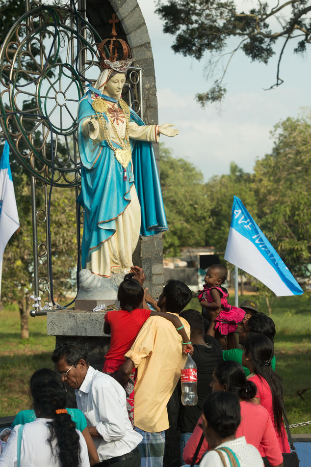 Catholic devotees touch a statue of the Virgin Mary as Pope Francis delivers a prayer at the church of Our Lady of Madhu in Madhu, Sri Lanka,Wednesday, Jan. ...