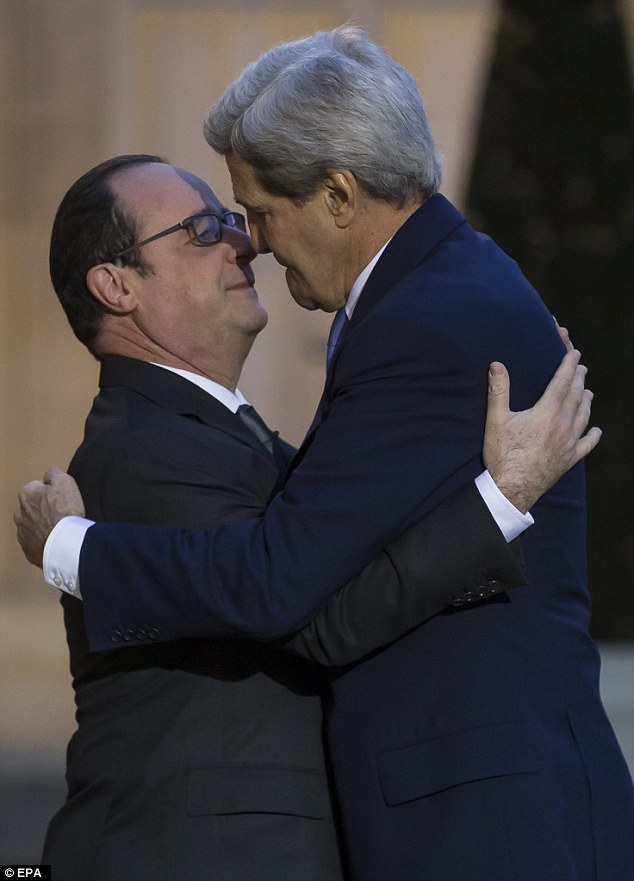 Close relationship: Secretary of State John Kerry leaned in to embrace French president Francois Hollande on a make-up visit after missing an enormous solidarity march last week