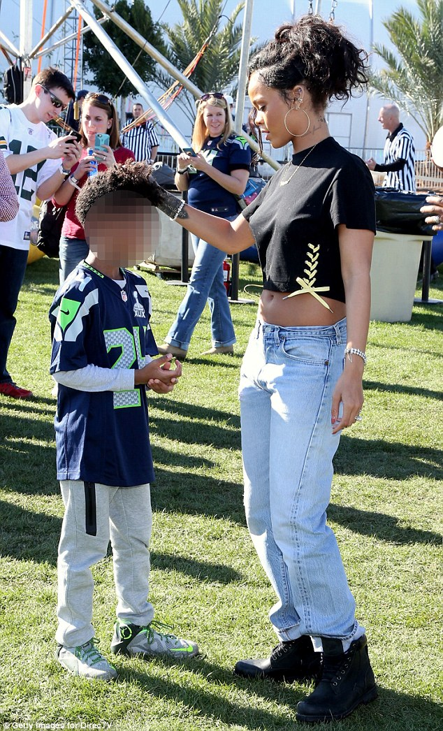 Affectionate: The Umbrella star played with a young Seattle Seahawks fan's hair