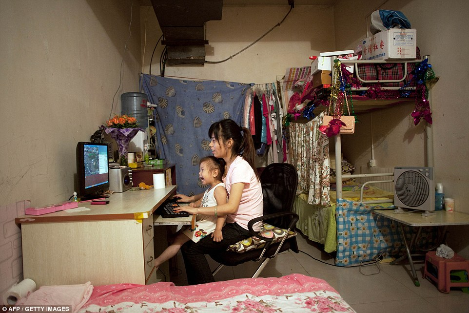 An alternative: Twenty-five-year-old Ji Lanlan and her three-year-old daughter, Yu Qi, enjoy a game on their computer in one of the largest rooms in this basement in west Beijing, China. The units were built in 1969 under Chairman Mao who feared a Soviet Attack