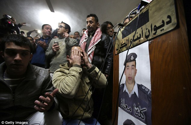 A bereaved man prays with verses of Quran at the Kasasbeh tribe society for Muath Al Kasasbeh, after hearing the news of his execution
