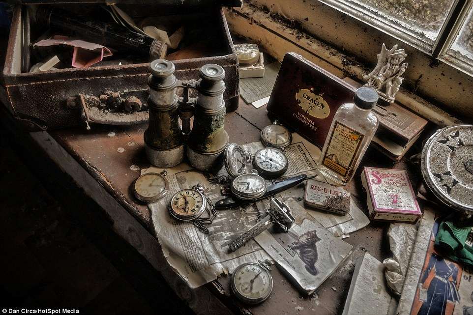 A dark wooden chest of drawers, home to a collection of pocket watches, is left inside the abandoned farmhouse