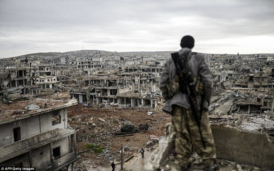 Musa, a Kurdish marksman, looks at the eastern part of the destroyed Syrian town of Kobane