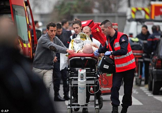 Impactante: Una persona lesionada es transportado a una ambulancia después del ataque terrorista Charlie Hebdo en el Janaury
