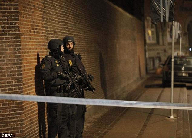 Lockdown: Policía Armada (en la foto) fueron fotografiados patrullando la zona en la noche del sábado mientras helicópteros sobrevolaban la zona y la ciudad entró en bloqueo.  Los residentes fueron advertidos por la policía para estar atentos y mantenerse en interiores