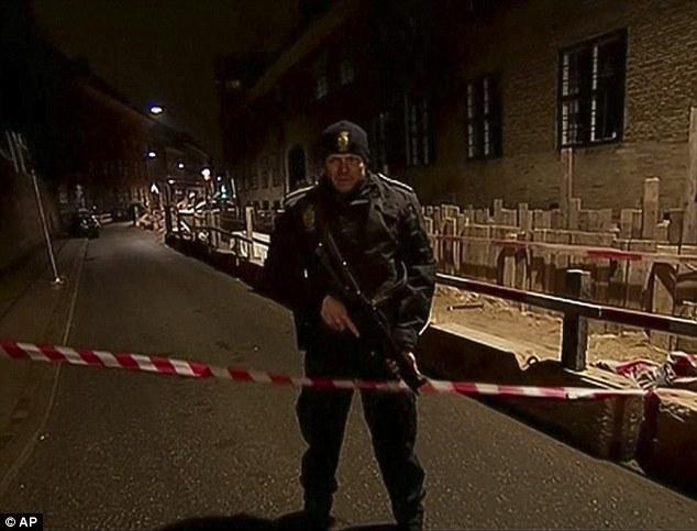 Un oficial de la policía armada está detrás de la cinta de la policía cerca de la sinagoga judía en el centro de Copenhague