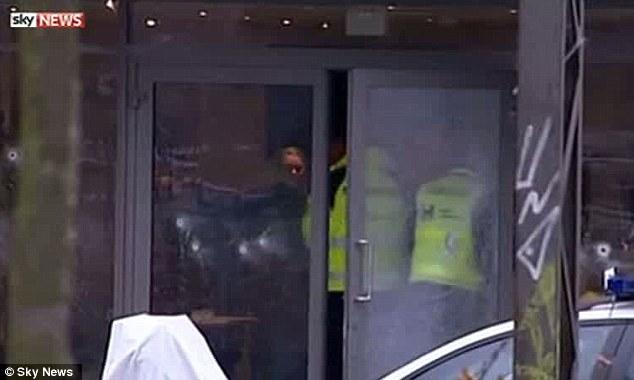 Los investigadores habían estado observando la propiedad en el barrio de Norrebro de Copenhague cuando el hombre salió.  Por encima, los funcionarios encuesta de la escena esta mañana después de que se reveló que el hombre era el culpable creído de los tiroteos de lobo solitario