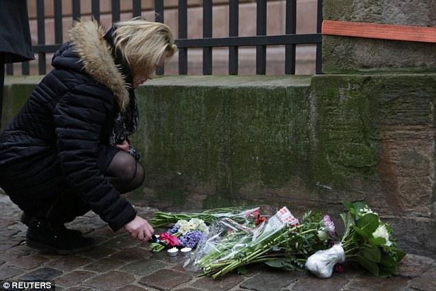 Las velas y las flores se quedaron fuera del edificio en el que el hombre judío recibió un disparo en la cabeza y murió en las primeras horas de esta mañana