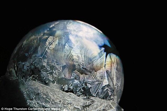 Reflexiones: Esta burbuja de hielo notable parece un planeta congelado colgando en el espacio sin estrellas