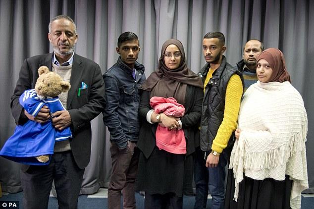Sr. Hussen, izquierda, posa para una foto con la familia de Shamima Begum en la sede de Scotland Yard, Londres