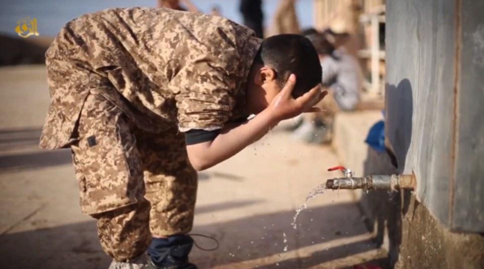 Un joven se ve ablución realización, un proceso ritual requerido antes de la oración, en el último vídeo de propaganda de Estado Islámico