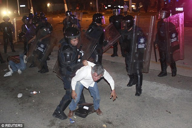 Federal policemen detain a member of CETEG (State Coordinator of Teachers of Guerrero) after demonstrators blocked the main access to the airport in Acapulco