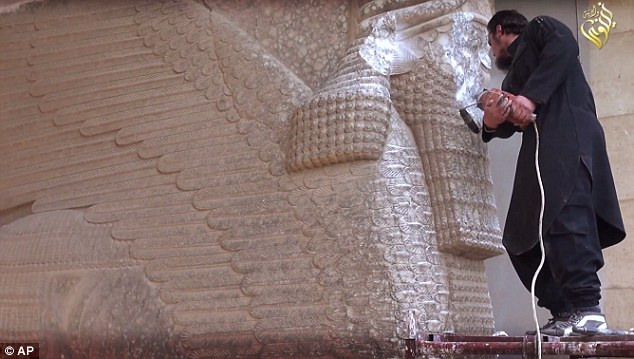 Militant uses a power tool to destroy a winged-bull Assyrian protective deity at the Ninevah Museum in Mosul, Iraq. The statue dates back to the 9th century B.C.