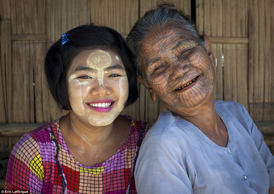 Generation gap: AlthoughMa Aung Seim has facial tattoos, her granddaughter Yi Yi (left) has refused to have them for fear of ridicule
