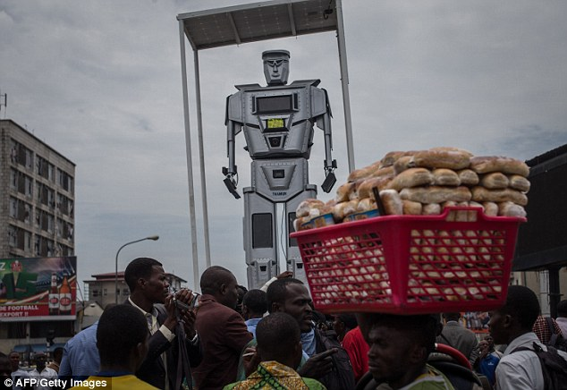 The 8ft solar-powered aluminium robots are huge, towering over the jammed streets of Kinshasa, as cars and motorcyles jostle for road room, their horns blasting