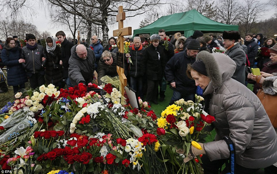 Hundreds of floral tributes including bunches of red roses were left on the grave of the murdered Russian opposition leader  after a burial ceremony