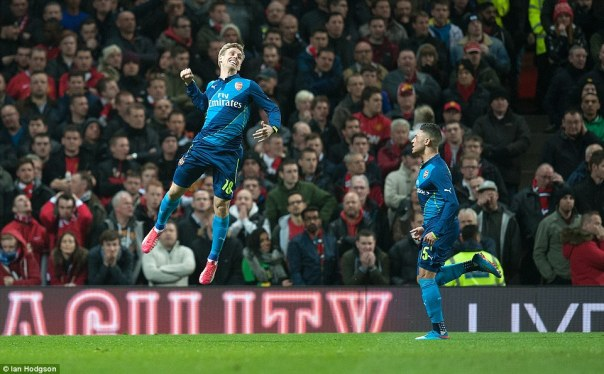 Arsenal left back Nacho Monreal jumps in the air after putting his side in the lead as Alex-Oxlade Chamberlain watches on