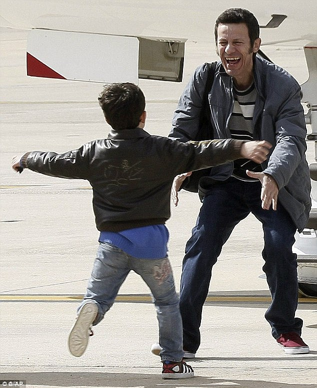 Freed: The moment journalist Javier Espinosa was reunited with his son on the tarmac of a Spanish airport after spending months in captivity, held by ISIS terrorists