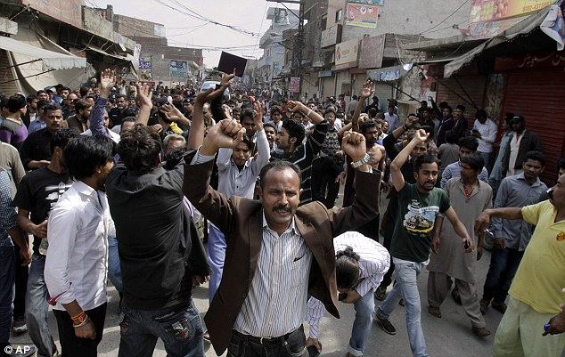 Pakistani Christians chant slogans near the site of suicide bombing attack on two churches in Lahore