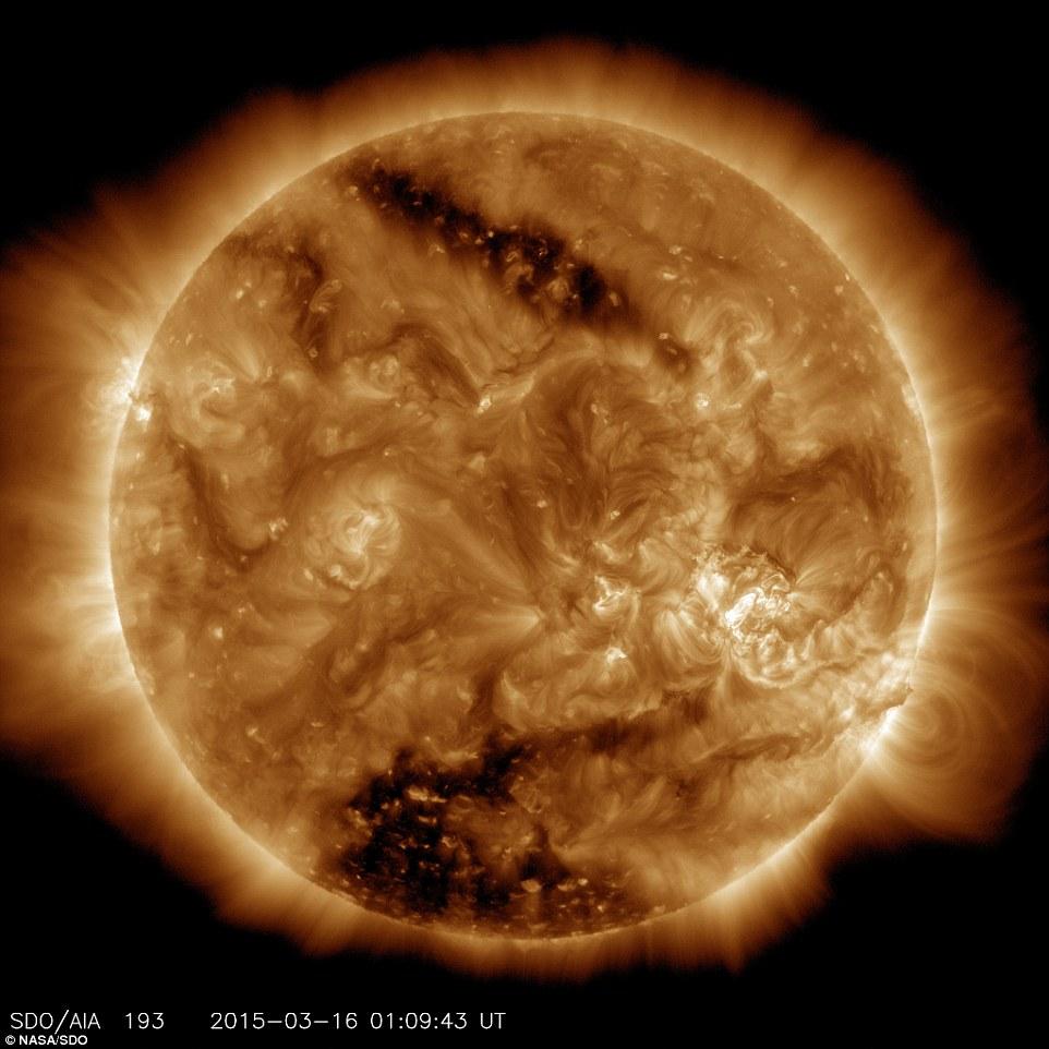 Observatorio de Dinámica Solar, o SDO de la NASA, capturó esta imagen solar el 16 de marzo de 2015, lo que muestra claramente dos manchas oscuras, conocidas como agujeros coronales.