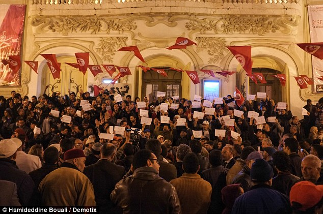 More than 1,000 Tunisians gathered outside the building in a late-night vigil to pay their respects to those murdered