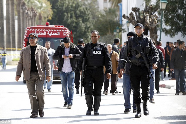 Tunisian authorities said yesterday they had arrested nine people suspected of helping the two gunmen. Pictured: Police officers march through the streets of Tunis in the wake of the deady attacks