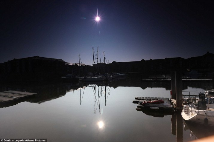Still: Sharp spring sunshine was dulled by the eclipse over Swansea Marina in South Wales today