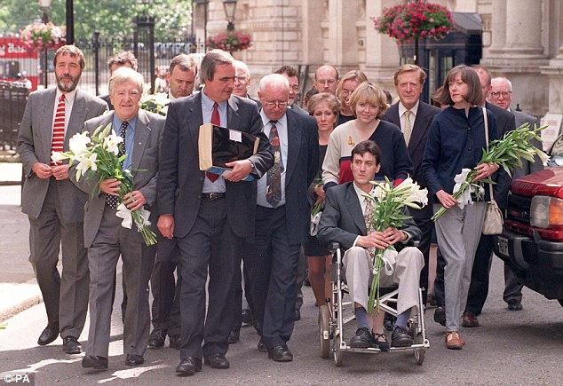 Long fight: Members of theHaemophilia Society delegation delivered a petition to David Cameron, along with lilies to represent people that have died as a result of being given infected blood