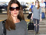 Ashley Greene wore a long gray sweater with black jeans for her flight into Los Angeles.  The star traveled light, carrying her own bags, on Friday, March 27, 2015 X17online.com