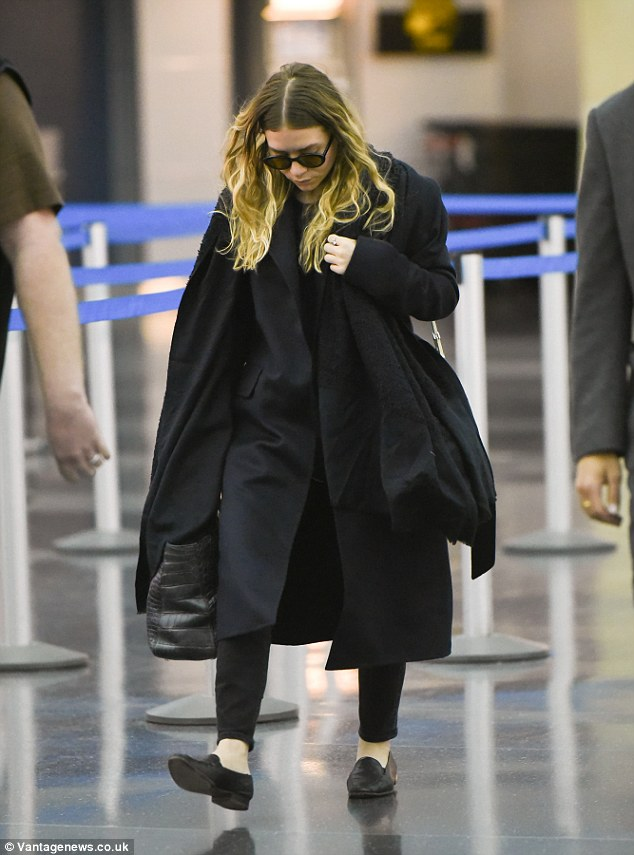 Singnature style: For her flight, Ashley donned a pair of cropped straight leg pants with a black T-shirt, trench coat and a long black pashmina