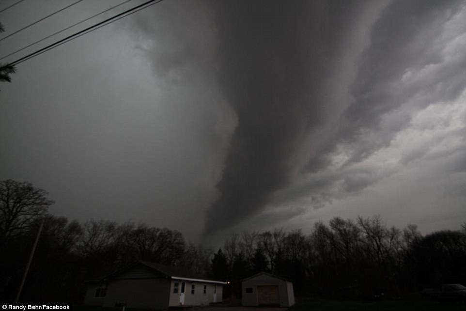 Menace: A dark funnel cloud is seen in the sky over central Illinois Thursday