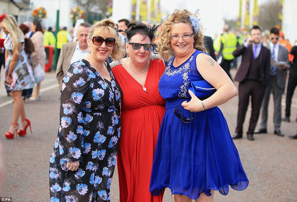 Ready for action: Three ladies arrive for their day out at the races sporting pretty dresses in patriotic red and blue