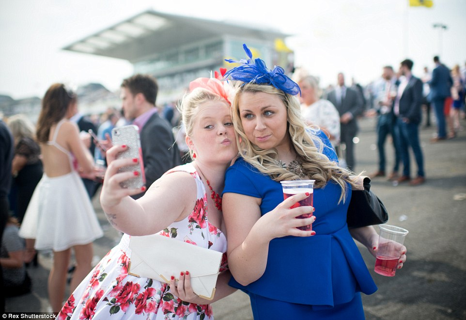 Mwah! Two ladies pose for a selfie and manage to juggle brightly coloured cocktails at the same time