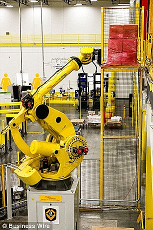 A Kiva robot is shown moving goods  and another robot unloading them, which is placed in a safety cage