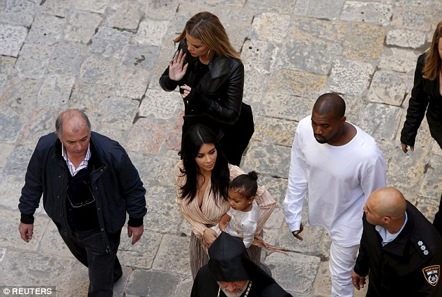 Famous: The family walk on the grounds of the Cathedral of Saint James in Jerusalem's Old City on Monday