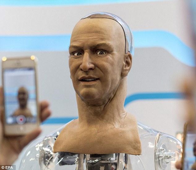 Αντιδραστική: Το ρομπότ χαμόγελα χρήση πολλαπλών κινητήρων - που whir σε δράση και διακριτικά ρυθμίσετε πολλαπλά σημεία άρθρωσης γύρω από το στόμα του και καστανά μάτια