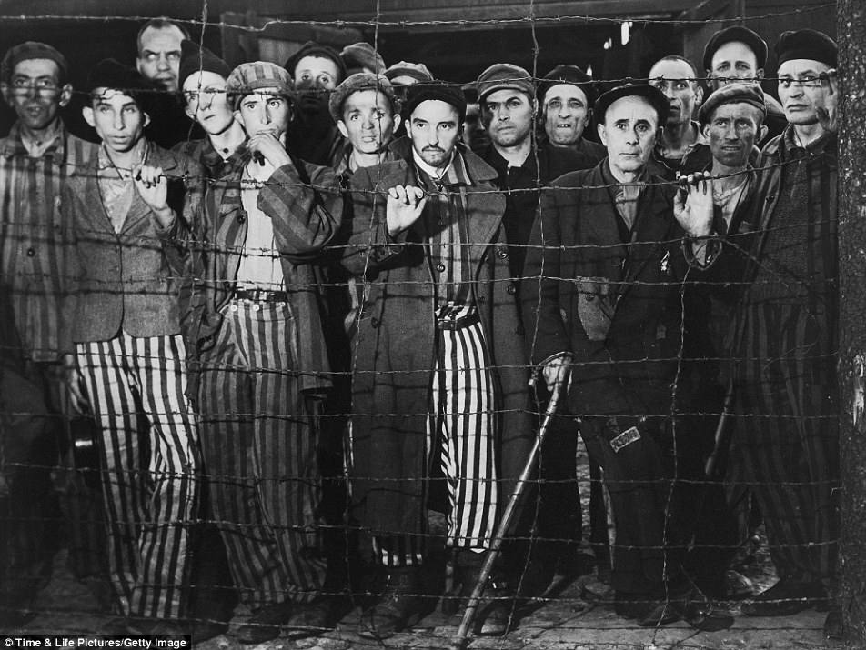 Emaciated male prisoners, victims of Nazi genocide, staring through barbed wire fence at their liberators after American forces overran the Buchenwald concentration camp