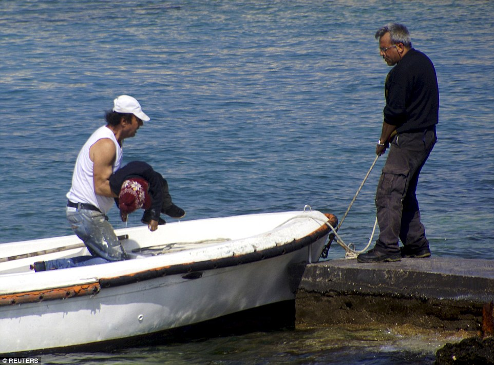 Horrendous sight: A man carries the body of a dead child onto the Greek island of Rhodes after a wooden sailing boat carrying dozens of people ran aground, killing at least three people in one of a number of tragedies involving migrant vessels over the last two days