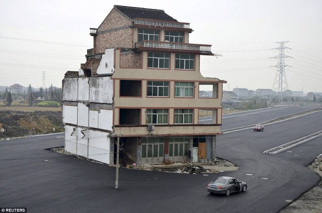 Last house standing: A car stops beside a house in the middle of a newly built road in Wenling, Zhejiang provinc