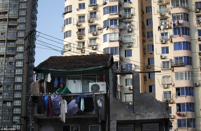 A woman stands at the balcony of her house which will be demolished to build new apartments in downtown Shanghai