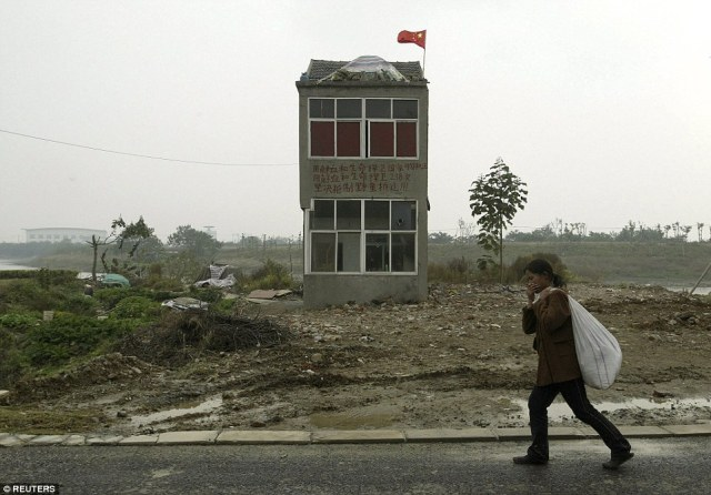 A woman walks past a nail house, the last house in this area, on the outskirts of Nanjing, Jiangsu province
