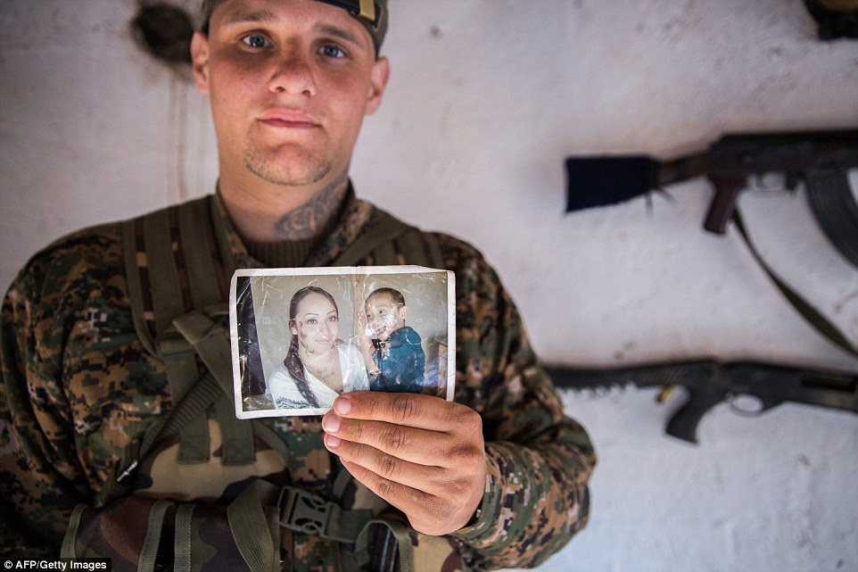 Remembering family: A 26-year old from the U.S., nick-named  Hewal Dilsad by Kurdish fighters, shows a picture of his wife and son