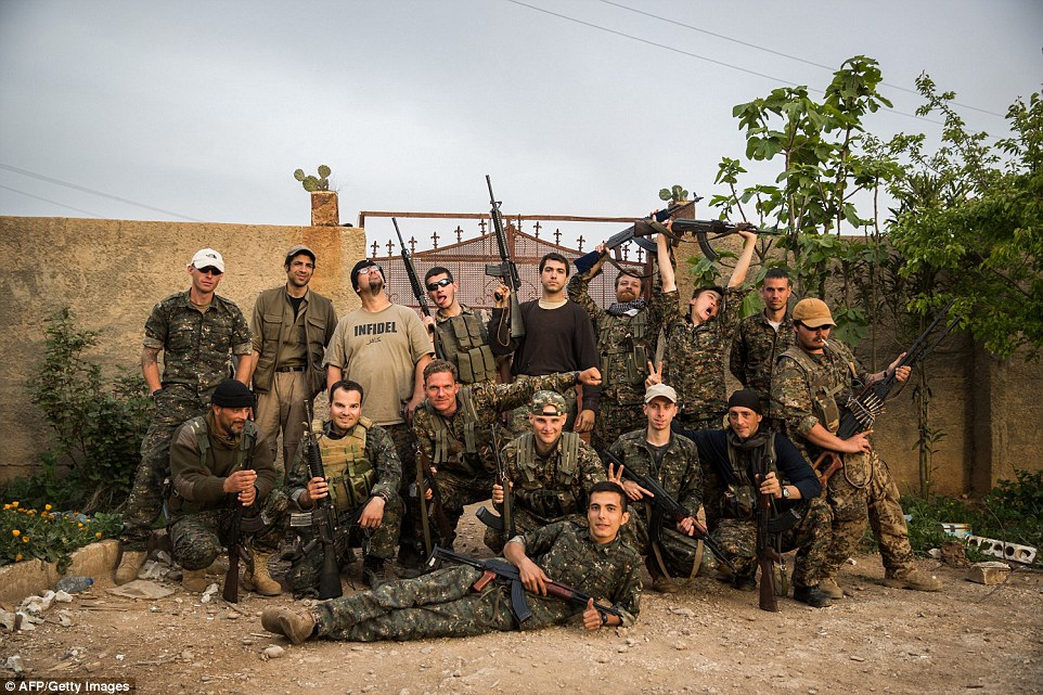 Light-hearted: The  international fighters pose for a photograph in the outskirts of the north-west Syrian town of Tal Tamr earlier this week