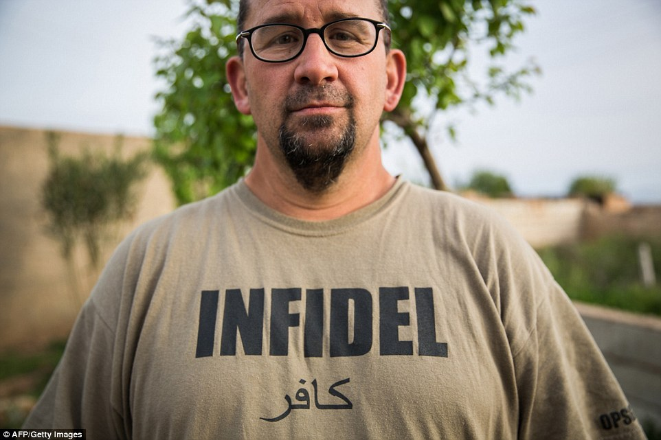 No surrender: A 38-year-old American national calling himself Hewal Cekdar is seen wearing a khaki T-shirt emblazoned with the word 'Infidel' in both English and Arabic, in a show of defiance in the face of ISIS' brand of Islamic extremism
