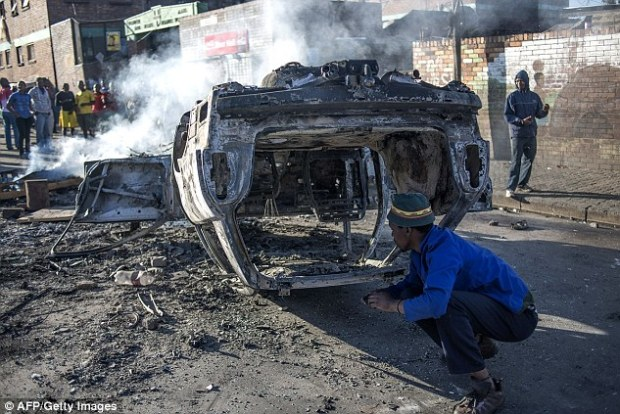 Frenzy: A burnt-out car in the Jeppestown area of Johannesburg. King Zwelithini recently told a crowd of 10,000 that if he had really ordered people to be killed 'this country would be reduced to ashes'